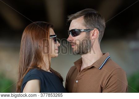 Cute Couple Man And Woman In Sunglasses Are Talking, Close-up. Summer Season In The Park.