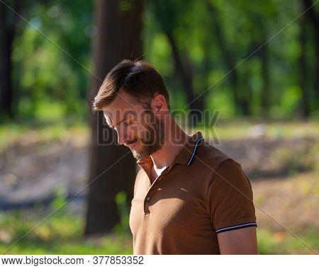 Handsome Bearded Man Looks Around. Summer Season In The Park.