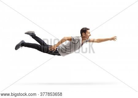 Full length profile shot of a casual young man flying and reaching for something isolated on white background