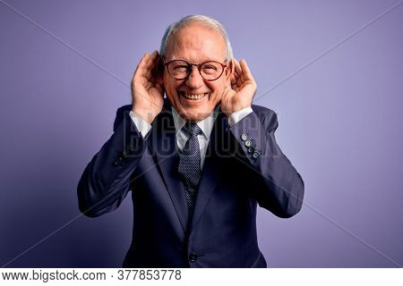 Grey haired senior business man wearing glasses and elegant suit and tie over purple background Trying to hear both hands on ear gesture, curious for gossip. Hearing problem, deaf