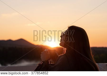 Girl With Closed Eyes Drinking Coffee Contemplating Views At Sunset