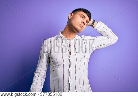 Young handsome hispanic man wearing elegant business shirt standing over purple background confuse and wondering about question. Uncertain with doubt, thinking with hand on head. Pensive concept.