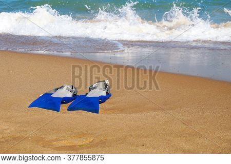 Flippers On The Sand Against The Background Of The Sea