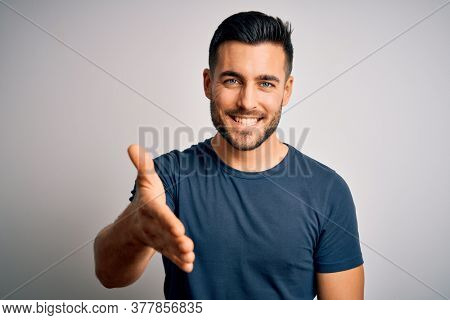 Young handsome man wearing casual t-shirt standing over isolated white background smiling friendly offering handshake as greeting and welcoming. Successful business.
