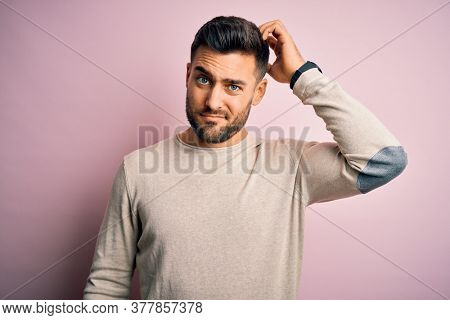 Young handsome man wearing casual sweater standing over isolated pink background confuse and wonder about question. Uncertain with doubt, thinking with hand on head. Pensive concept.