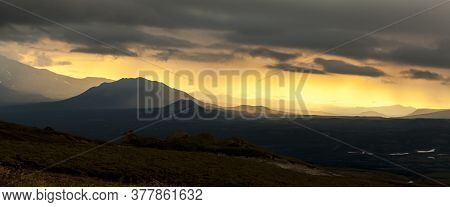 Sunset In The Mountains, The Rays Of The Sun Breaking Through The Clouds. Kamchatka Peninsula, Russi