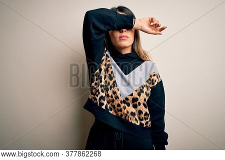 Young beautiful woman wearing casual sweatshirt standing over isolated white background covering eyes with arm, looking serious and sad. Sightless, hiding and rejection concept