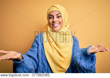 Young beautiful brunette muslim woman wearing arab hijab over isolated yellow background smiling cheerful with open arms as friendly welcome, positive and confident greetings
