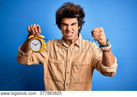 Young handsome man holding alarm clock standing over isolated blue background annoyed and frustrated shouting with anger, crazy and yelling with raised hand, anger concept