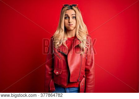 Young beautiful blonde woman wearing casual jacket standing over isolated red background puffing cheeks with funny face. Mouth inflated with air, crazy expression.