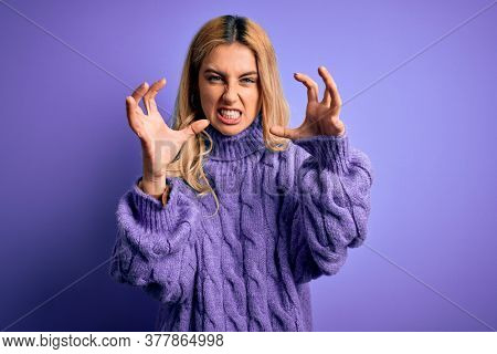 Young beautiful blonde woman wearing casual turtleneck sweater over purple background Shouting frustrated with rage, hands trying to strangle, yelling mad