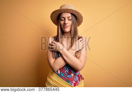 Young beautiful blonde woman wearing swimsuit and summer hat over yellow background Hugging oneself happy and positive, smiling confident. Self love and self care