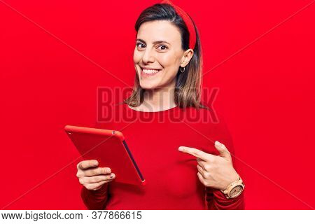 Young beautiful woman holding touchpad smiling happy pointing with hand and finger