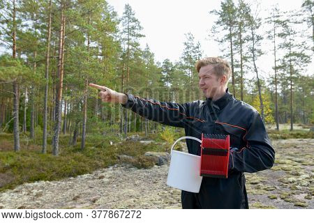 Portrait Of Happy Young Handsome Man Pointing Finger While Holding Bucket And Berry Picker In The Fo
