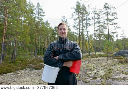 Portrait Of Happy Young Handsome Man With Bucket And Berry Picker In The Forest