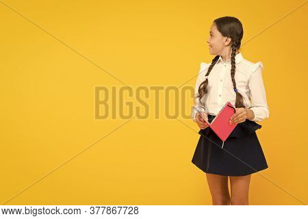 Learning Language And Literature. Cute Small Child Holding Book Of Childrens Literature On Yellow Ba