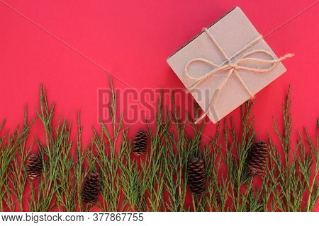 Brown Kraft Gift Box Tied With Twine, Cones And Evergreen Branches Frame On A Dark Burgundy Backgrou