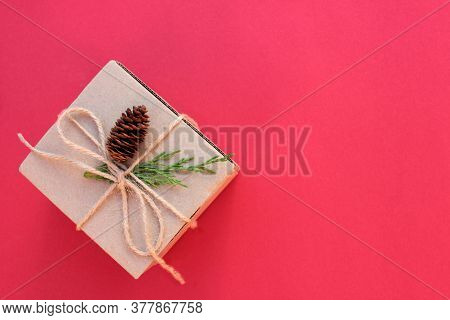 Brown Kraft Gift Box Tied With Twine And Decorated With A Cone And A Branch Of An Evergreen Bush On