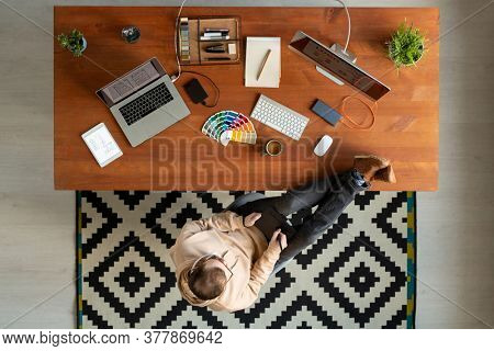 Directly above view of young man keeping feet on table and using drawing pad while working on graphic design