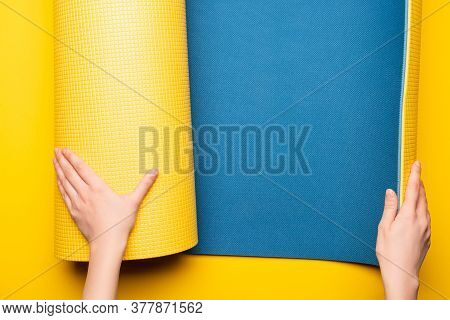 Partial View Of Woman Rolling Out Blue Fitness Mat On Yellow Background