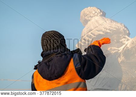 A Sculptor Of Ice Figures Cleans Snow From A Sculpture He Made. A Cropped Image. Rear View. Selectiv
