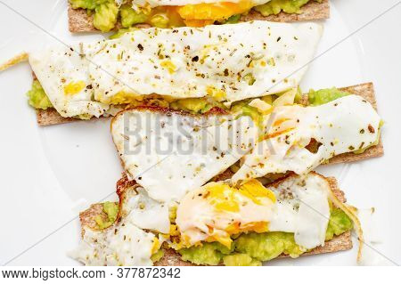 Bruschetta With Avocado And Poached Egg. Healthy Breakfast On A White Plate On The Kitchen Table.