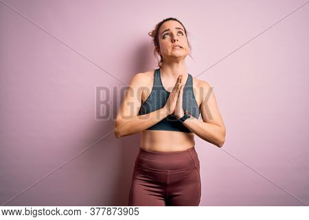 Young beautiful blonde sportswoman doing sport wearing sportswear over pink background begging and praying with hands together with hope expression on face very emotional and worried. Begging.