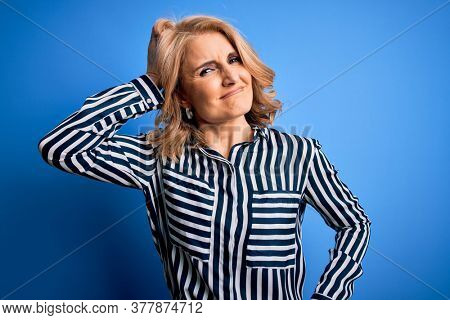 Middle age beautiful blonde woman wearing casual striped shirt standing over blue background confuse and wonder about question. Uncertain with doubt, thinking with hand on head. Pensive concept.