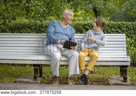 Portrait Of Grandfather And Grandson In The Park In Summer With A Tablet In His Hands, Grandfather U