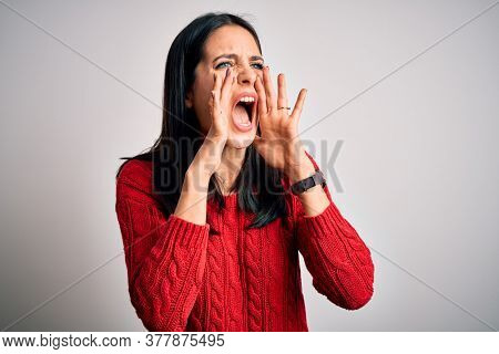 Young brunette woman with blue eyes wearing casual sweater over isolated white background Shouting angry out loud with hands over mouth