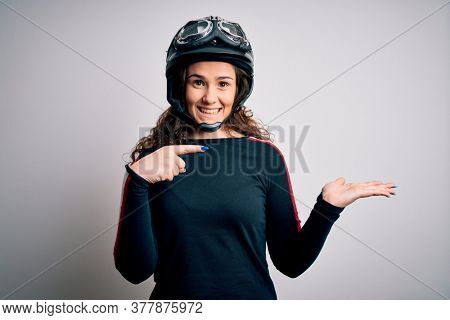 Beautiful motorcyclist woman with curly hair wearing moto helmet over white background amazed and smiling to the camera while presenting with hand and pointing with finger.