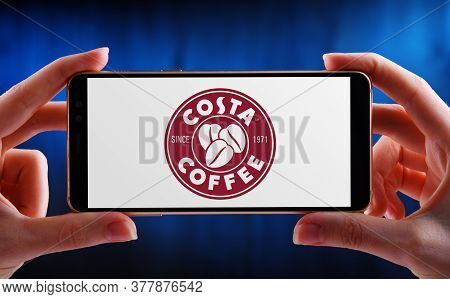 Hands Holding Smartphone Displaying Logo Of Costa Coffee