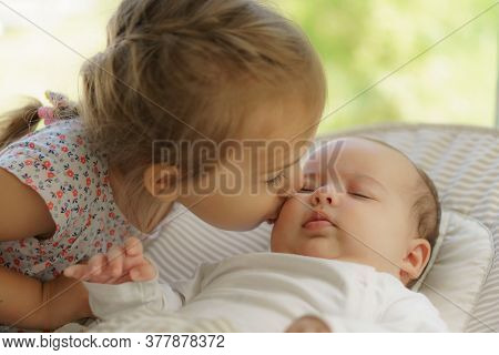 Cute Little Girl Kissing His Newborn Sister. Toddler Kid Meeting New Born Sibling. Infant Sleeping I