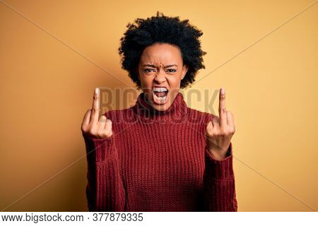 Young beautiful African American afro woman with curly hair wearing casual turtleneck sweater Showing middle finger doing fuck you bad expression, provocation and rude attitude. Screaming excited