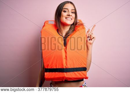 Young beautiful brunette woman wearing orange lifejacket over isolated pink background with a big smile on face, pointing with hand and finger to the side looking at the camera.