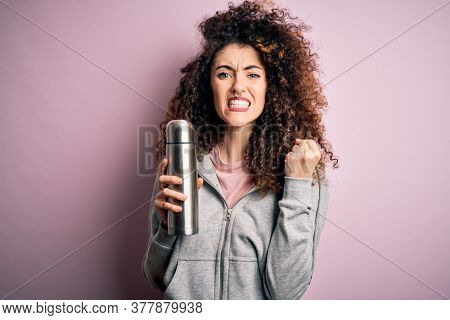 Young beautiful tourist woman with curly hair and piercing holding thermo with water annoyed and frustrated shouting with anger, crazy and yelling with raised hand, anger concept