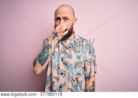 Handsome bald man with beard and tattoo wearing casual floral shirt over pink background smelling something stinky and disgusting, intolerable smell, holding breath with fingers on nose. Bad smell