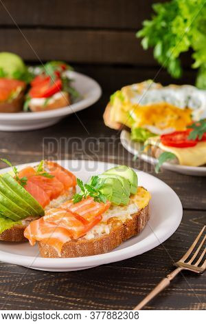 Different Delicious Sandwiches For Breakfast, Bread With Cheese, Avocado And Trout, Sandwich With Eg