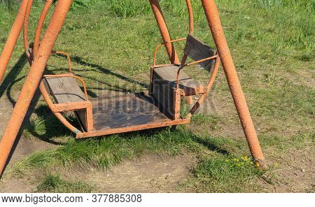 Old Rusty Swing On The Grass. Empty Swings, The Concept Of Kidnapping.
