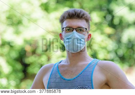 Young Man With A Medical Mask On His Face On A Natural Green Background