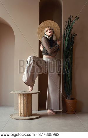 Gorgeous Blonde Girl In Straw Hat, Blouse And Wide Trousers Posing Near Tall Succulent Plant, Holdin