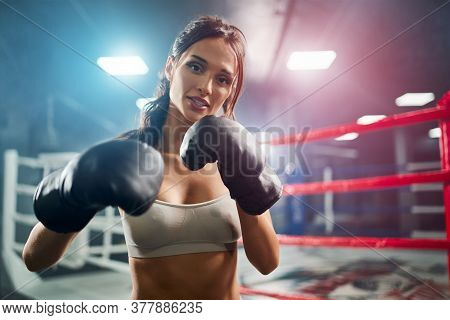 Front View Of Fit Smiling Brunette Woman Wearing Boxing Gloves. Young Attractive Fighter With Perfec