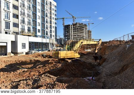 Excavator On Earthworks For Laying Heating Pipes And Stormwater In Trench. Installing Concrete Wells