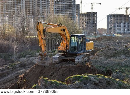 Excavator Working At Construction Site On Earthworks. Backhoe Digging Building Foundatio. Constructi