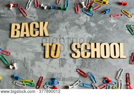 Inscription Back To School Of Wooden Letters On A Gray Background. Concrete Background. Words And Sy