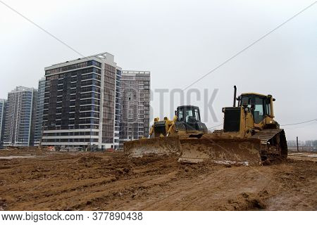 Group Of Dozers With Buckets At Construction Site. Bulldozer During Land Clearing, Grading, Pool Exc