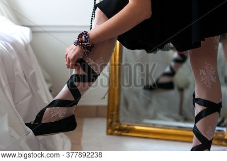 Trying On Clothes For The Party. The Girl Tries On Stylish Youth Clothes At The Mirror. Ties Shoes W