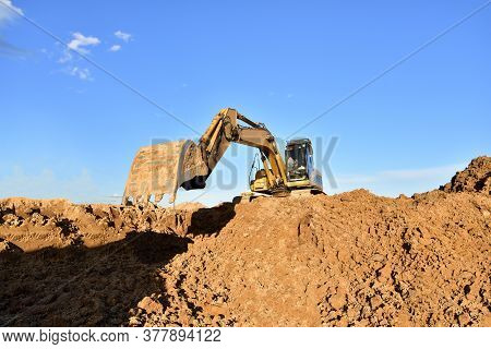 Excavator Working On Earthmoving At Open Pit Mining. Backhoe Digs Gravel In Quarry. Construction Mac