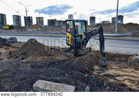 Mini Excavator During Road Work At Construction Site. Screeding Sand For Installing Borders, Curbs A
