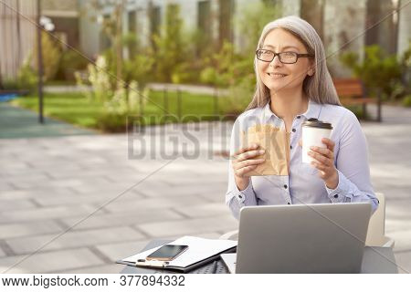 Working Online. Portrait Of A Happy Mature Business Woman Wearing Eyeglasses Having A Lunch, Drinkin